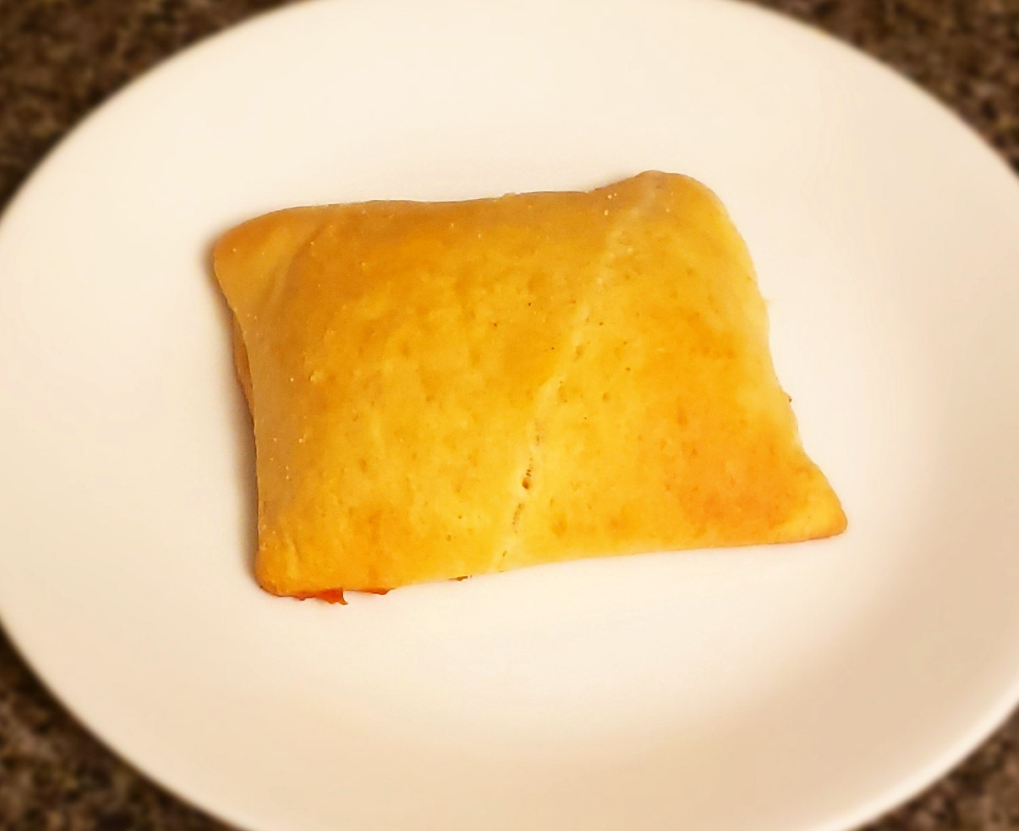 A square piece of golden brown baked pastry dough on a while plate